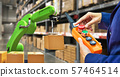 Industrial robot holding a box and worker operating a robot machine on stock shelves background 57464514