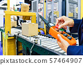 Manager check and control automation cardboard boxes on conveyor belt in  warehouse. 57464907