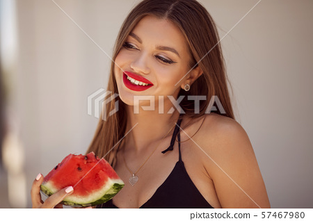 Fashion portrait of a sexy girl with perfect makeup is eating watermelon on the beach 57467980