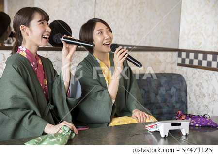 做一個婦女的旅行的婦女在卡拉OK演唱在溫泉旅館的卡拉OK演唱室休息室 57471125