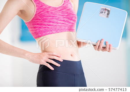woman hold weight scale 57477413