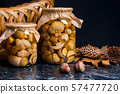 Two glass jars with wild marinated mushrooms on 57477720