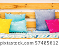 Close up pillows on an outdoor patio chair, with a blue striped cushioned bench 57485612