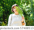 Young woman is hiding her eyes with fern leaf.  57488513