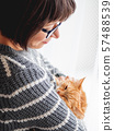 Cute ginger cat dozing on woman arms. Smiling woman in grey knitted sweater stroking her fluffy pet. Cozy home. 57488539