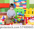 Toddler boy is playing in kidsroom with colorful constructor. Educational toy block in his hands. Kid is busy with toy bricks. 57489665
