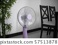 Modern violet electric fan in a living room saving peoples from hot temperature in summer days. 57513878