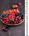 Fresh organic summer berries mix in round wooden 57515281