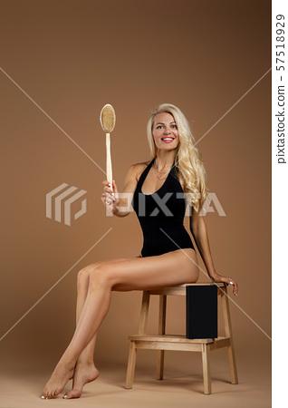 beautiful woman making a scrub massage with big brush. 57518929