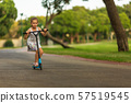 Little child learning to ride a scooter in a city park on sunny summer day 57519545