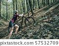 Photo of female athlete in helmet raising bicycle to hill in forest 57532709
