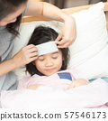 Mother attach cooling fever patch gel for reduce temperature her daughter at home. 57546173
