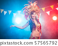 Carnival, belly dance and holiday concept - Beautiful female samba dancer wearing gold costume and 57565792