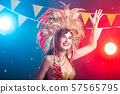Cabaret, dancer and holidays concept - Cute young girl in bright colorful carnival costume on dark 57565795