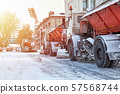 Snow plow removing snow from the city road. Snowplow truck working in the street 57568744