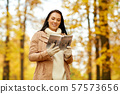 happy young woman with city guide in autumn park 57573656