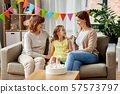 mother, daughter and grandmother at birthday party 57573797
