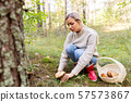 young woman picking mushrooms in autumn forest 57573867