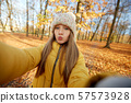girl taking selfie making duck face at autumn park 57573928