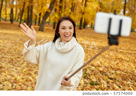 woman taking selfie by smartphone at autumn park 57574000