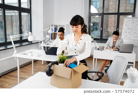 sad female office worker packing personal stuff 57574072