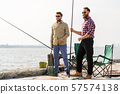 male friends with fishing rods and beer on pier 57574138
