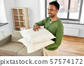 indian man with sofa cushions at new home 57574172