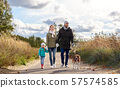 happy family walking with beagle dog in autumn 57574585