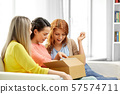 teenage girls or friends opening parcel box 57574711