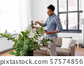 man spraying houseplant with water at home 57574856