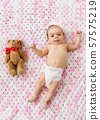 baby girl in diaper lying with teddy on blanket 57575219