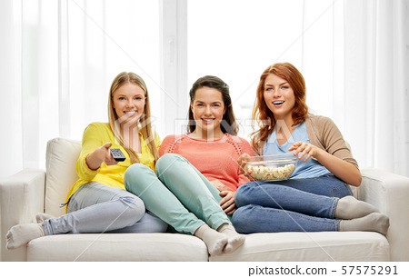teenage girls or friends watching tv at home 57575291