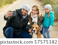 happy family with dog taking selfie in autumn 57575382