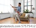 man with broom cleaning and having fun at home 57575412