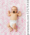 baby girl in diaper lying with pacifier on blanket 57575430