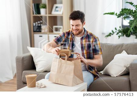 smiling man unpacking takeaway food at home 57576413