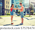 teenage couple riding skateboards on city street 57576474