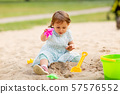 little baby girl plays with toys in sandbox 57576552