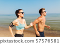 couple with phones and arm bands running on beach 57576581