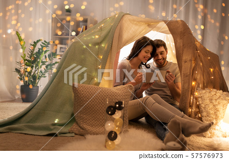couple drinking coffee or tea in kids tent at home 57576973