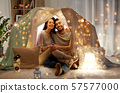 happy couple in kids tent at home 57577000