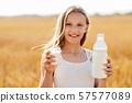 girl with bottle and glass of milk on cereal field 57577089