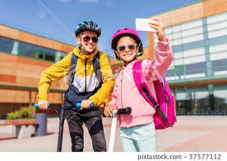 happy school kids with scooters taking selfie 57577112