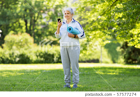 old woman with exercise mat and smartphone at park 57577274