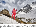 Portrait of hiking woman in red at the beautiful mountains background. 57577599