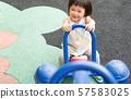Happy kid girl while playing seesaw swing  in kindergarten. 57583025