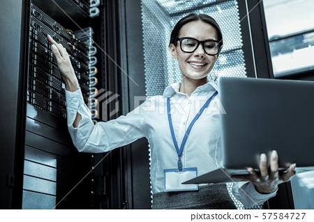 Dark-haired worker in black eyeglasses making revision of the equipment 57584727