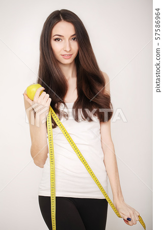 Diet. Girl on a diet measuring waist and abdomen centimeter and looks much fat. 57586964