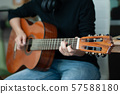 woman's hands playing acoustic guitar, close up 57588180