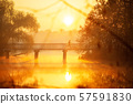 Man is running across bridge at sunrise. 57591830